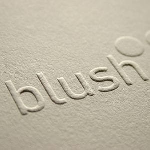 the word blush embossed on a paper card